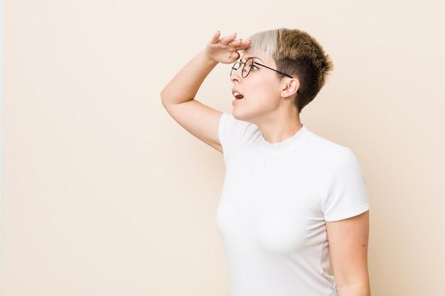 Giovane donna naturale autentica che porta una camicia bianca che sembra lontana che tiene mano sulla fronte.