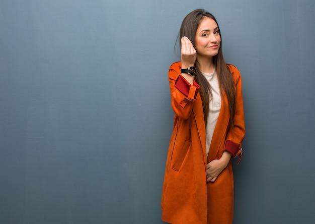 Giovane donna naturale che fa un tipico gesto italiano