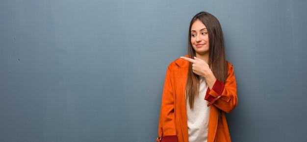 Giovane donna naturale che sorride e che indica il lato