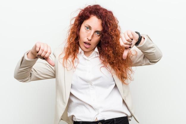 Giovane donna naturale di affari della testarossa contro la parete bianca che mostra pollice giù e che esprime avversione.