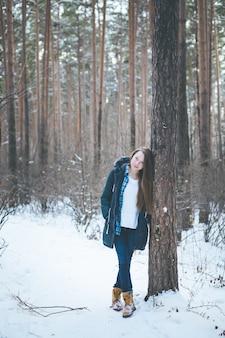Giovane donna naturale nella foresta di inverno