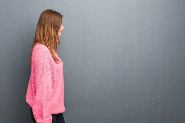 Giovane donna naturale russa dal lato che guarda alla parte anteriore