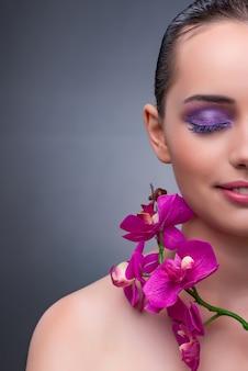 Giovane donna nel concetto di bellezza con fiore orchidea