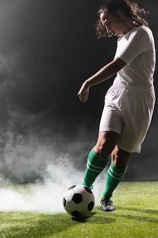 Giovane donna nel giocare a calcio degli abiti sportivi