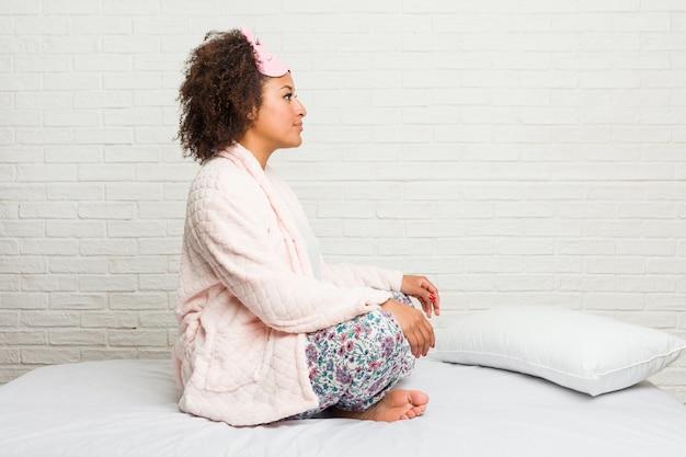 Giovane donna nel letto che indossa il pigiama guardando a sinistra, posa laterale.