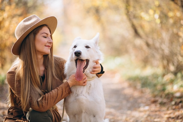 Giovane donna nel parco con il suo cane bianco