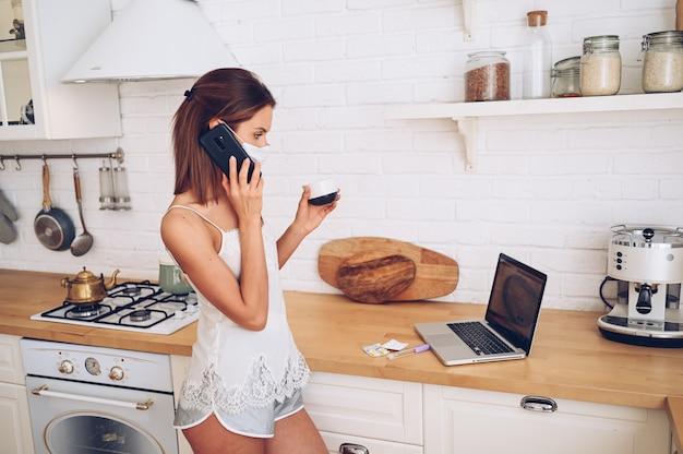 Giovane donna nel telefono parlante della maschera di protezione e lavorare ad un computer portatile con il caffè di mattina. quarantena domestica durante il virus della corona pandemica covid-19.