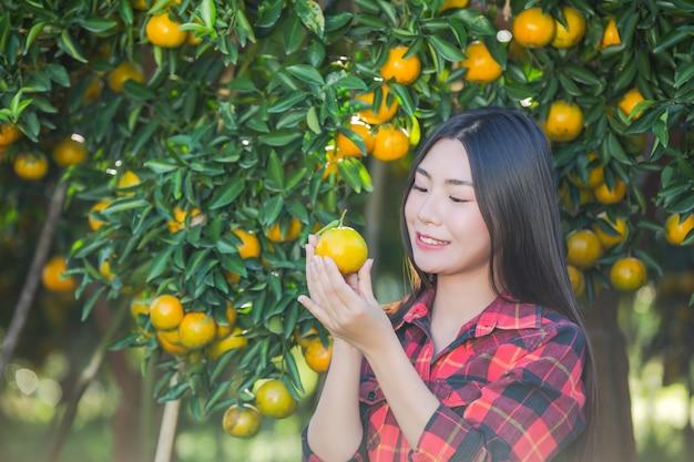 Giovane donna nell'arancia del raccolto del giardino nel giardino.