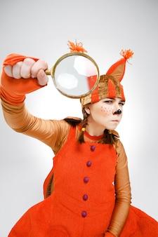 Giovane donna nell'immagine dello scoiattolo con la lente d'ingrandimento