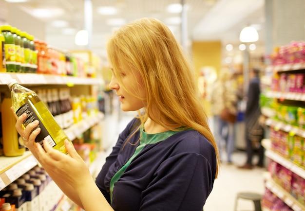 Giovane donna nell'iscrizione della lettura del supermercato