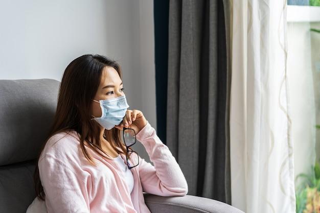 Giovane donna nella mascherina medica che si siede su un divano