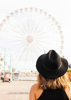 Giovane donna nella parte anteriore della grande ruota gigante