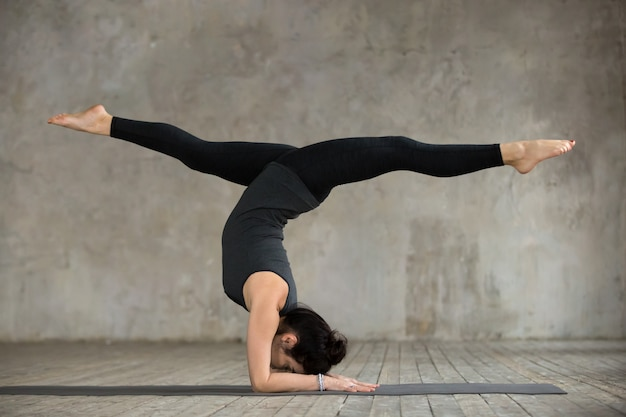 Giovane donna nella posa di handstand