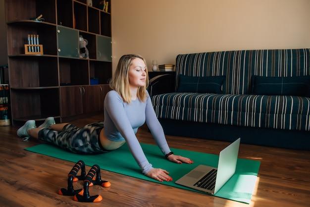 Giovane donna nella posa di yoga che guarda classe online a casa durante la quarantena. la ragazza esile attraente in abiti sportivi che fanno la forma fisica si esercita sulla stuoia.
