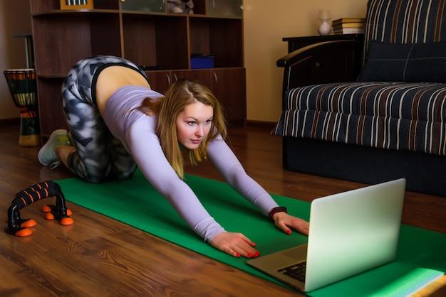 Giovane donna nella posa di yoga che guarda classe online a casa