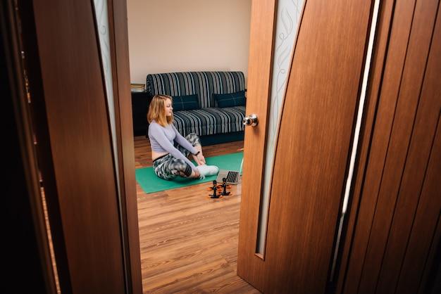 Giovane donna nella posa di yoga che guarda classe online nella sala