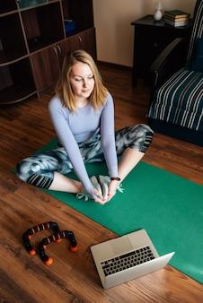 Giovane donna nella posa di yoga che guarda classe online