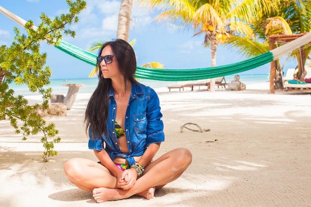 Giovane donna nella posizione di loto sulla spiaggia di sabbia bianca