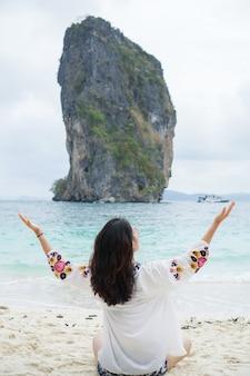 Giovane donna nella seduta felice sulla sabbia. tour itinerante in asia: krabi, tailandia.