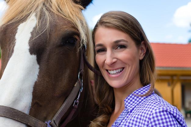 Giovane donna nella stalla con cavallo al sole