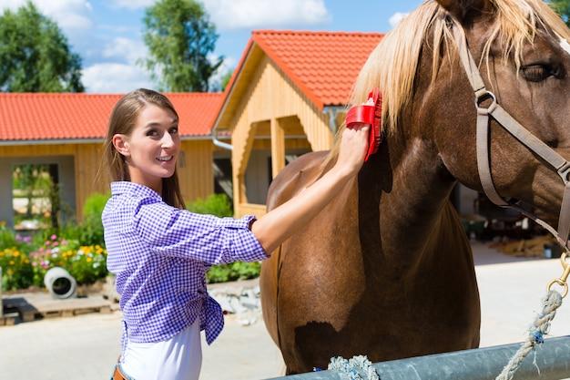 Giovane donna nella stalla con cavallo