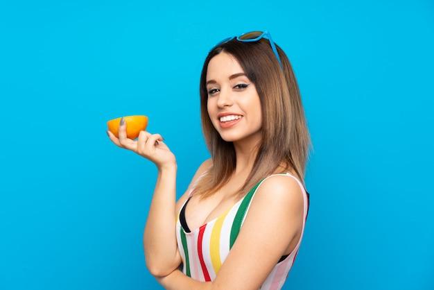 Giovane donna nelle vacanze estive sopra la parete blu che tiene un'arancia