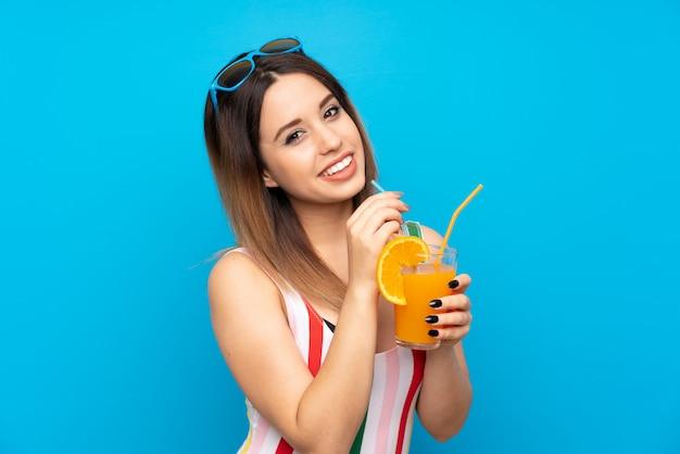 Giovane donna nelle vacanze estive sopra la parete blu con il cocktail