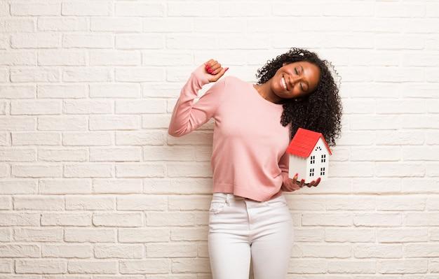Giovane donna nera ascoltando musica, ballando e divertendosi, muovendosi, gridando ed esprimendo felicità, concetto di libertà