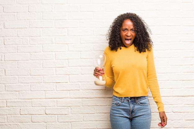 Giovane donna nera che grida arrabbiata, espressione di follia e instabilità mentale