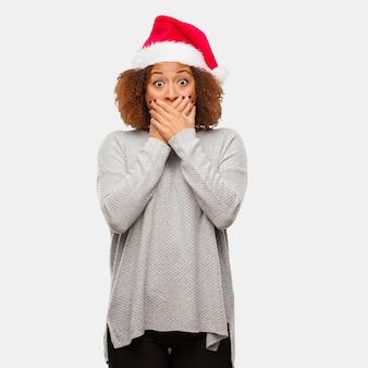 Giovane donna nera che indossa un cappello di santa sorpreso e scioccato