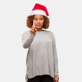 Giovane donna nera che indossa un cappello santa mostrando numero uno