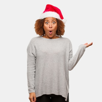 Giovane donna nera che indossa un cappello santa tenendo qualcosa sulla mano di palma
