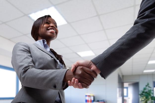 Giovane donna nera di affari che agita le mani con un uomo d'affari
