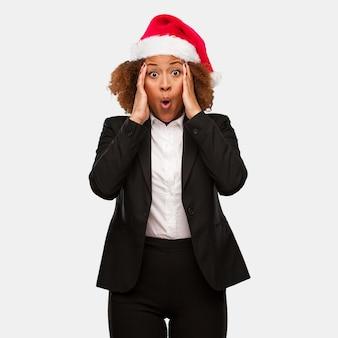 Giovane donna nera di affari che indossa un cappello di santa di chirstmas sorpreso e colpito
