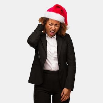 Giovane donna nera di affari che indossa un dolore al collo sofferenza del cappello di santa di chirstmas