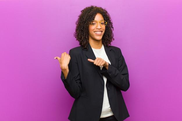 Giovane donna nera di affari che sorride allegramente e casualmente indicando per copiare lo spazio dal lato, sentendosi felice e soddisfatto