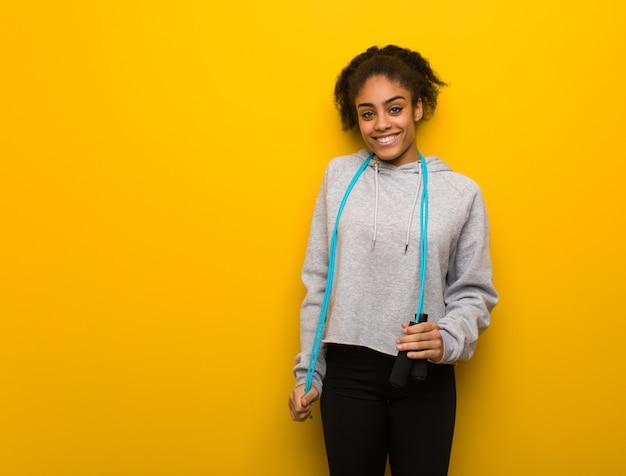 Giovane donna nera di forma fisica allegra con un grande sorriso. tenendo una corda per saltare.
