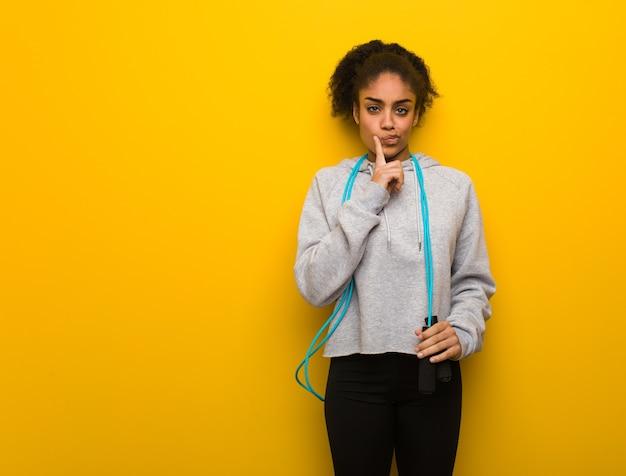 Giovane donna nera di forma fisica che dubita e confusa. tenendo una corda per saltare.
