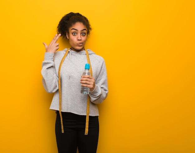 Giovane donna nera di forma fisica che fa un gesto di suicidio. che tiene una bottiglia di acqua.