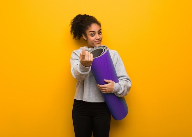 Giovane donna nera di forma fisica che invita a venire. in possesso di un tappetino.