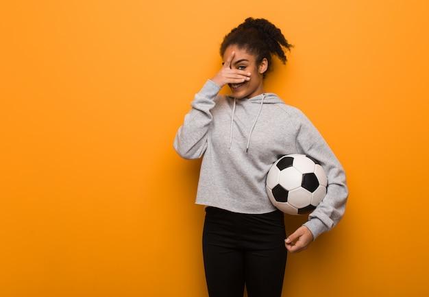 Giovane donna nera di forma fisica imbarazzata e ridendo allo stesso tempo. in possesso di un pallone da calcio.