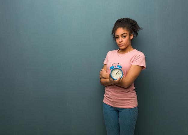 Giovane donna nera guardando dritto. tiene in mano una sveglia.