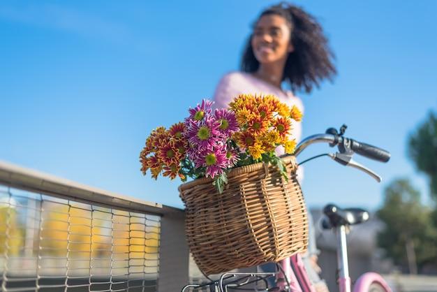 Giovane donna nera in sella a una bicicletta d'epoca
