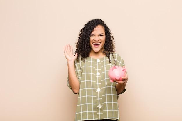 Giovane donna nera sentirsi felice, eccitata, sorpresa o scioccata, sorridente e stupita per qualcosa di incredibile che tiene un salvadanaio