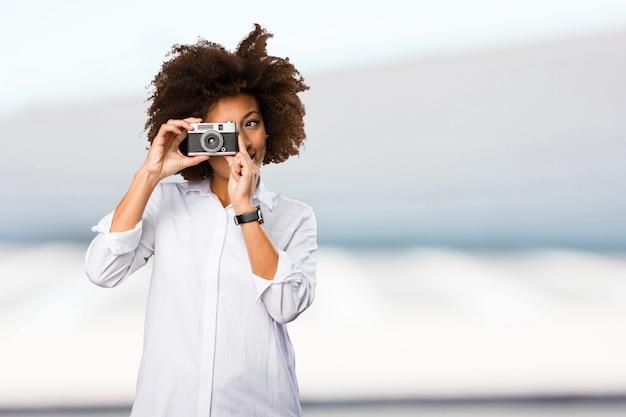 Giovane donna nera utilizzando una macchina fotografica d'epoca