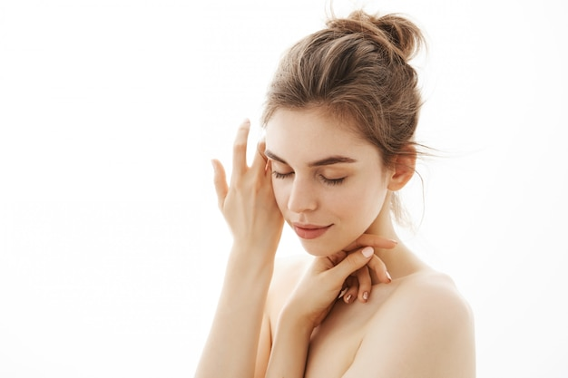 Giovane donna nuda tenera con il panino che posa sopra il fondo bianco. occhi chiusi.