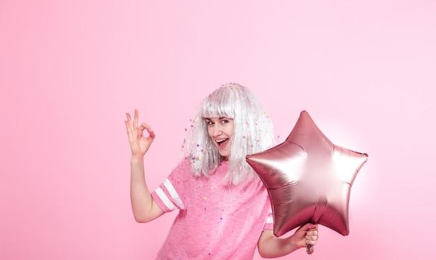 Giovane donna o ragazza con palloncini e mostra due dita. concetto di festa.