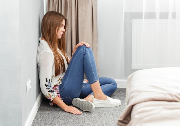 Giovane donna o ragazza seduta sul tappeto a casa