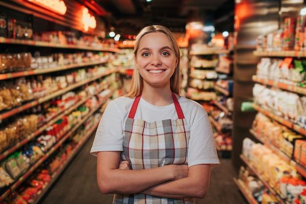 Giovane donna occupata che sta nella linea fra gli shelfs con pasta