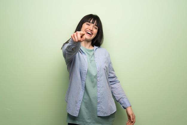 Giovane donna oltre muro verde che puntava il dito contro qualcuno e ridendo molto